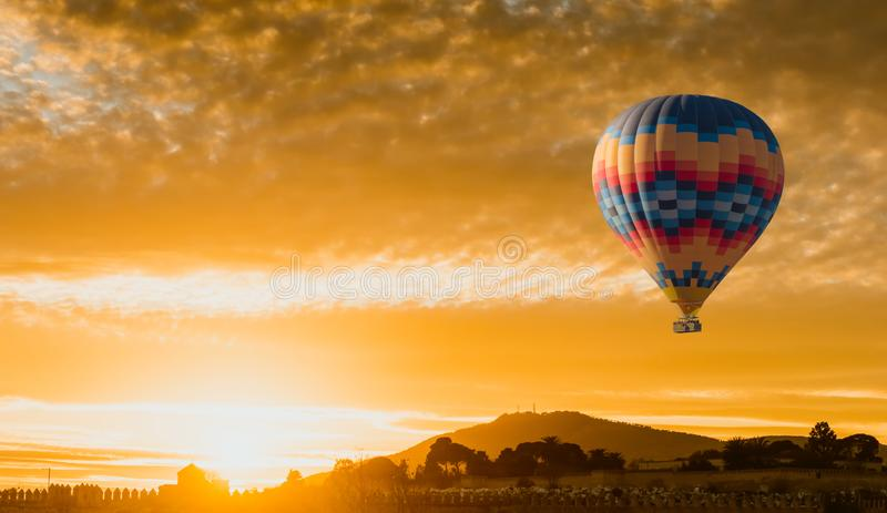Hot air balloon flying at yellow sunrise royalty free stock images