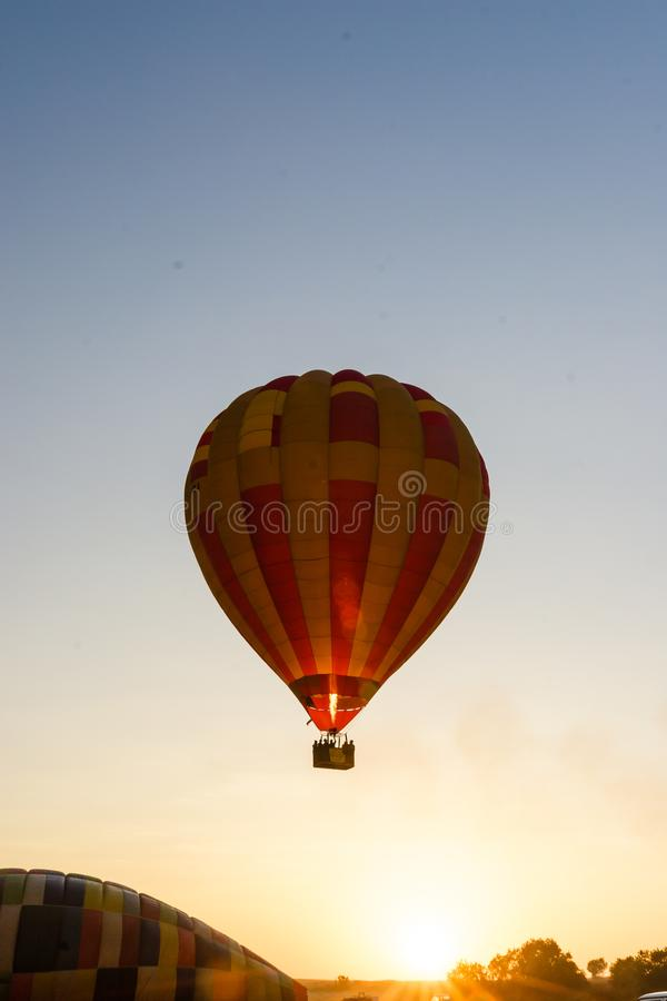 A hot air balloon takes off from the ground. A hot air balloon is heated and takes off from the ground. The balloon is being heated and is starting to float, up stock photos