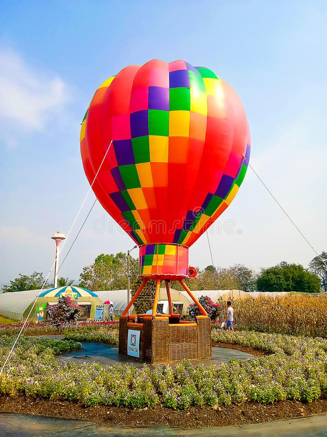 Hot air balloon over cosmos flowers with blue sky royalty free stock photography