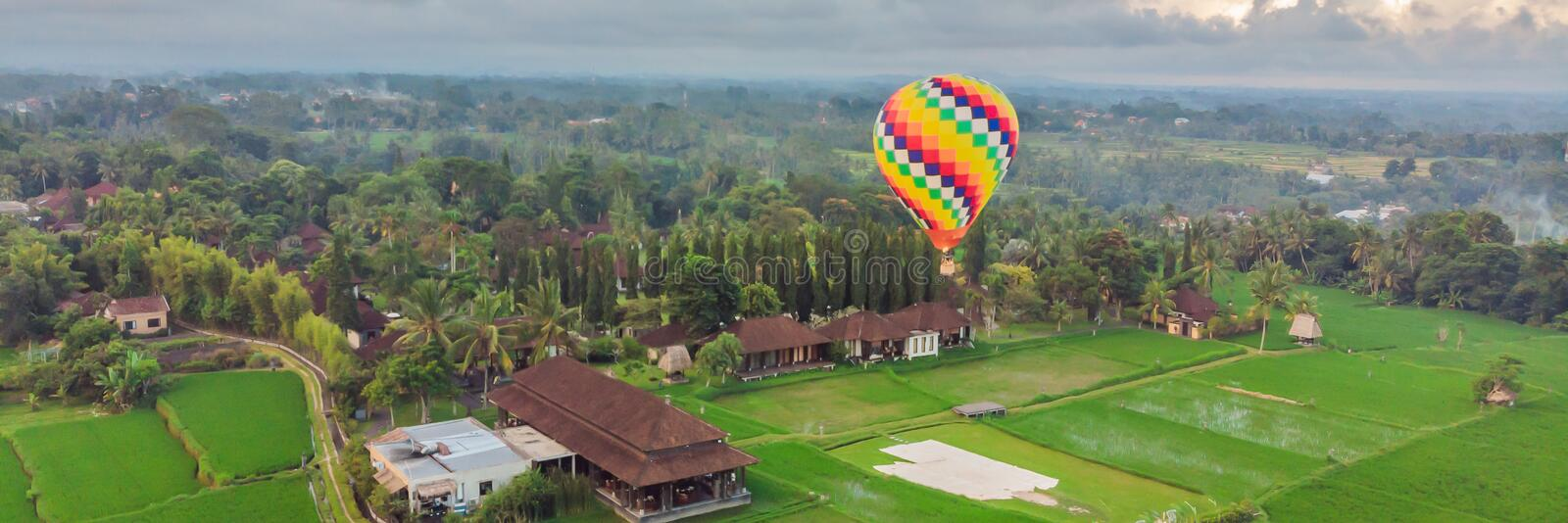 Hot air balloon over the green paddy field. Composition of nature and blue sky background. Travel concept BANNER, LONG stock image