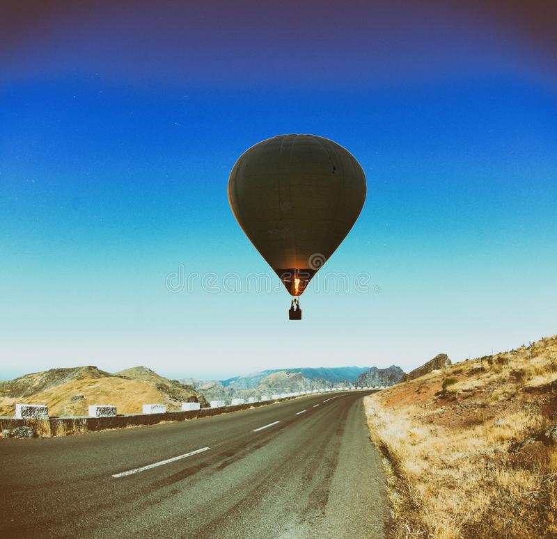 Hot air balloon over a road stock images