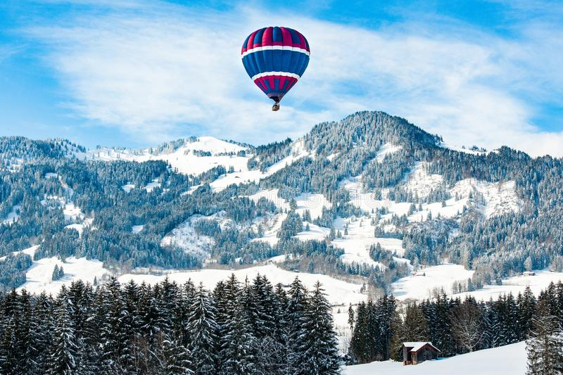 Hot-air balloon over snow covered landscape in Pre-Alps, Bavaria, Germany. Hot-air balloon over hills in snow covered pre-alpine andscape on beautiful day with stock photography