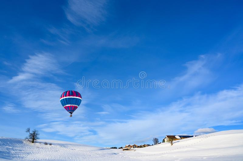 Hot-air balloon over snow covered landscape and small rural village, Bavaria, Germany. Hot-air balloon over hills and houses in snow covered landscape on royalty free stock images