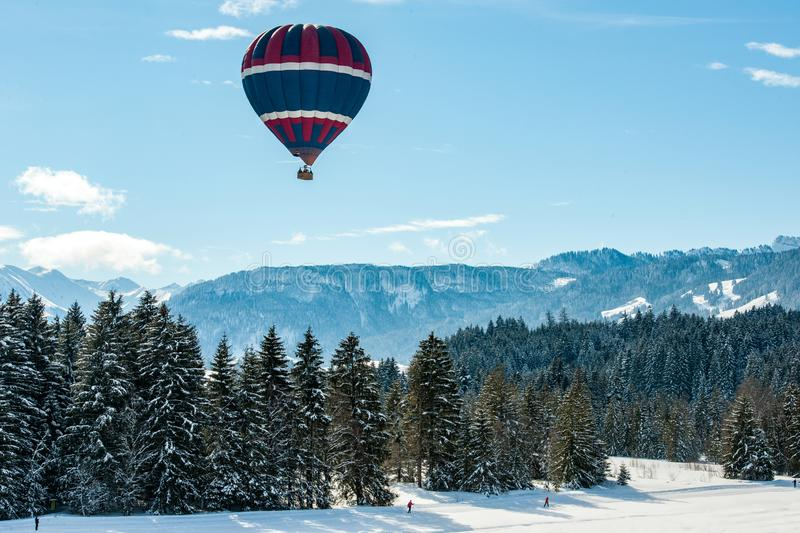 Hot-air balloon over snow covered slope and Pre-Alps, Bavaria, Germany stock images