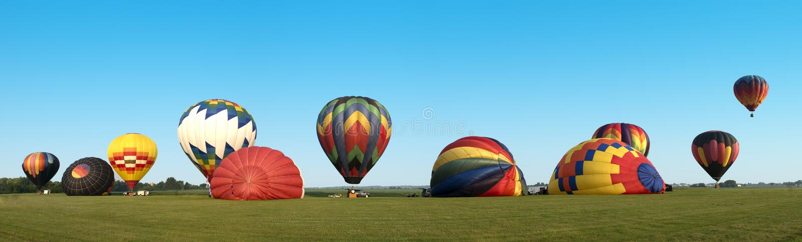 Hot Air Balloon Panoama Panoramic Banner. Balloons at a hot air balloon festival are in a line and are preparing to launch for a morning flight. The colorful royalty free stock photo