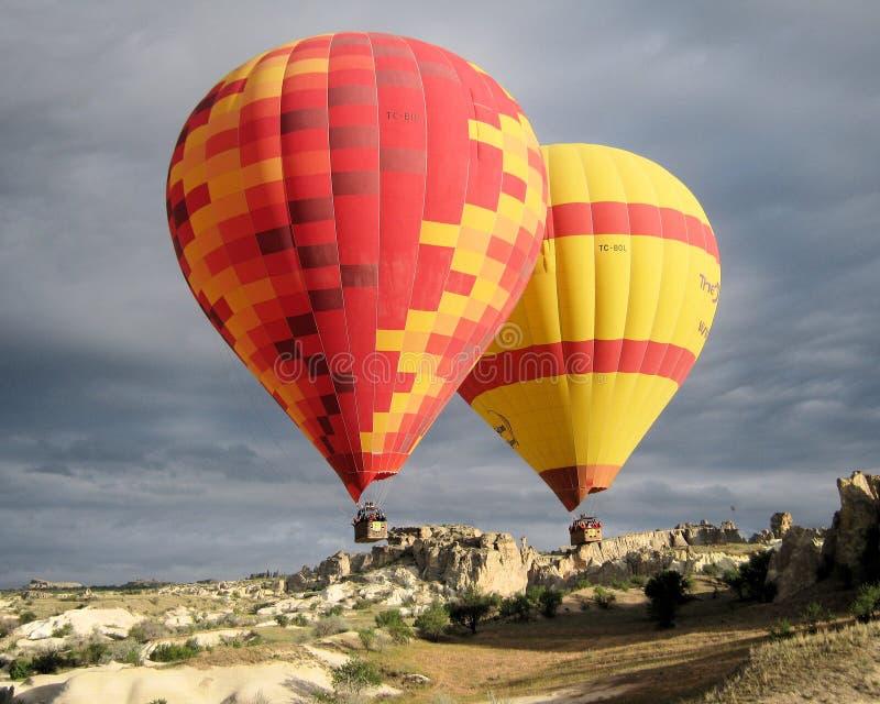 Hot air balloon ride with dark clouds - Cappadocia - Turkey. Cappadocia Turkey Two red yellow colored hot air balloons during ballooning with dark clouds and royalty free stock photos