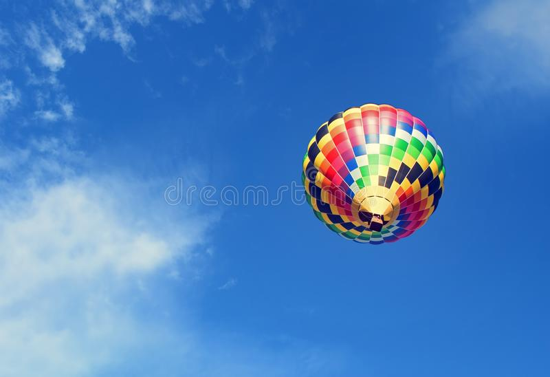 Hot air balloon is rising up to the blue sky stock photography