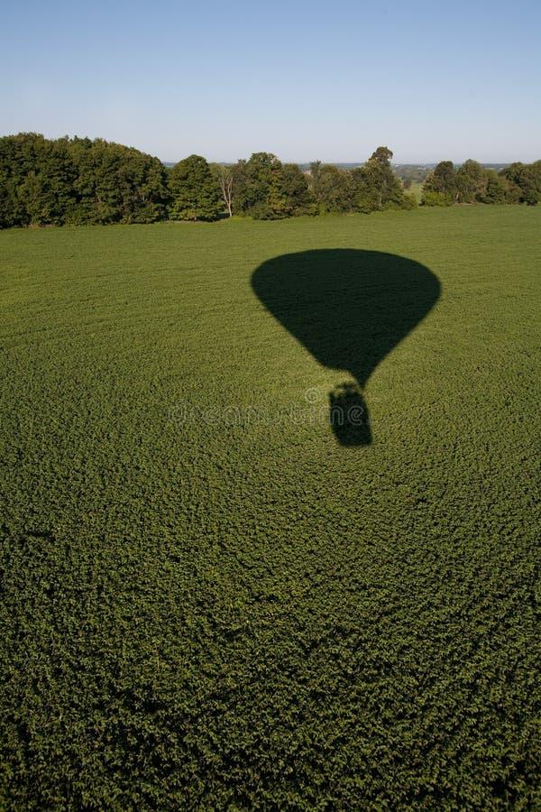 Hot air balloon shadow on field. stock photo