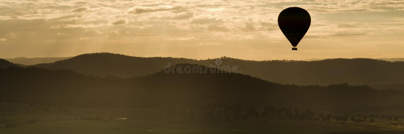 Hot air balloon silhouette. Silhouette panorama of a hot air balloon floating over hilly countryside at sunset royalty free stock photography