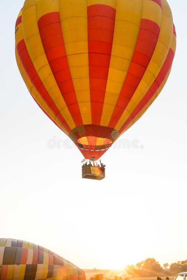 A hot air balloon takes off from the ground. A hot air balloon is heated and takes off from the ground. The balloon is being heated and is starting to float, up stock photo