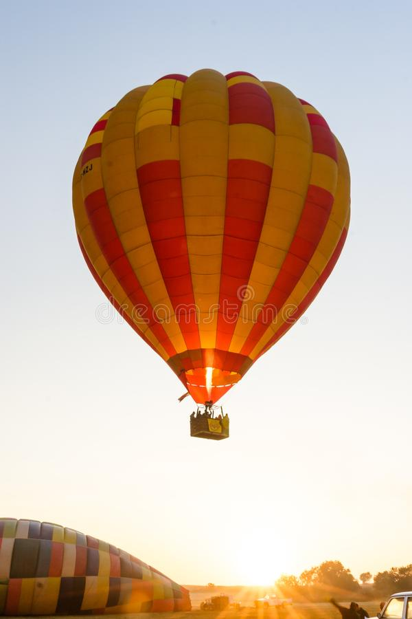 A hot air balloon takes off from the ground. A hot air balloon is heated and takes off from the ground. The balloon is being heated and is starting to float, up stock image