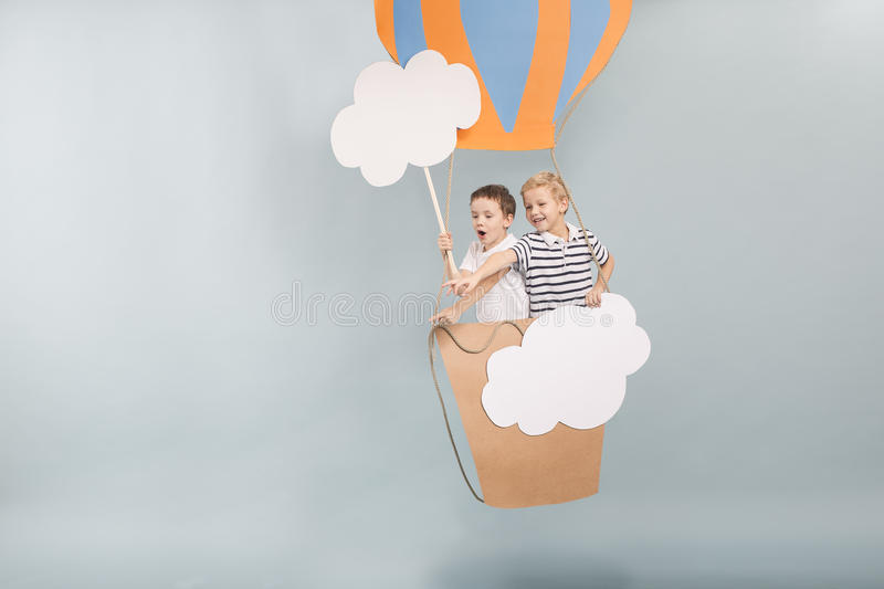 Hot air balloon. Two little happy boys in the paper hot air balloon stock photos