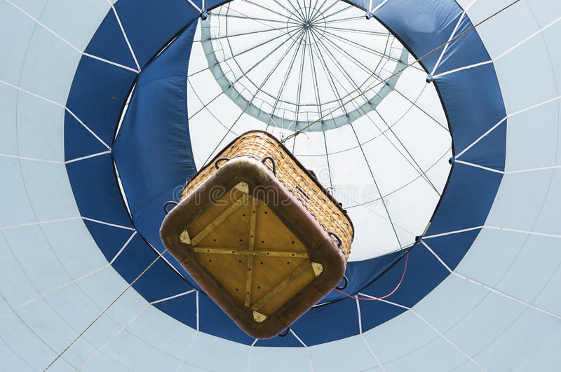 Hot air balloon. Suspended hot air balloon with passenger carrying basket viewed from below stock photos