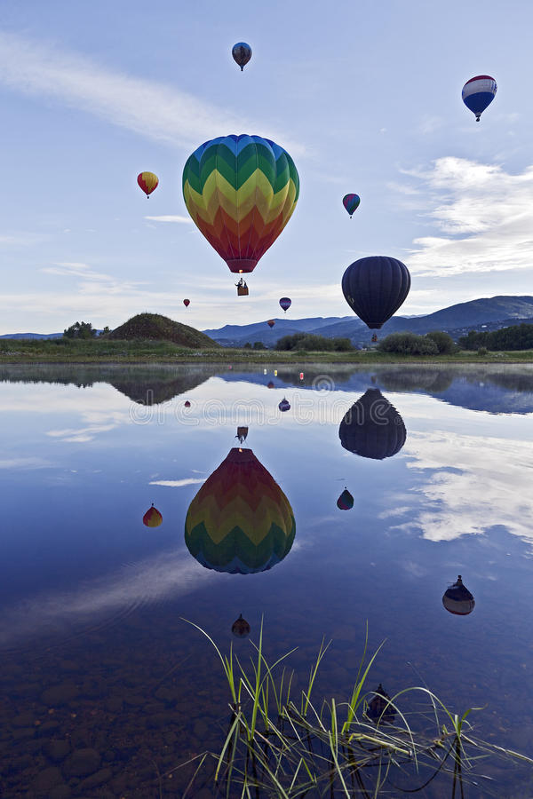 Hot Air Balloons. Number of hot air balloons launching over a lake stock image