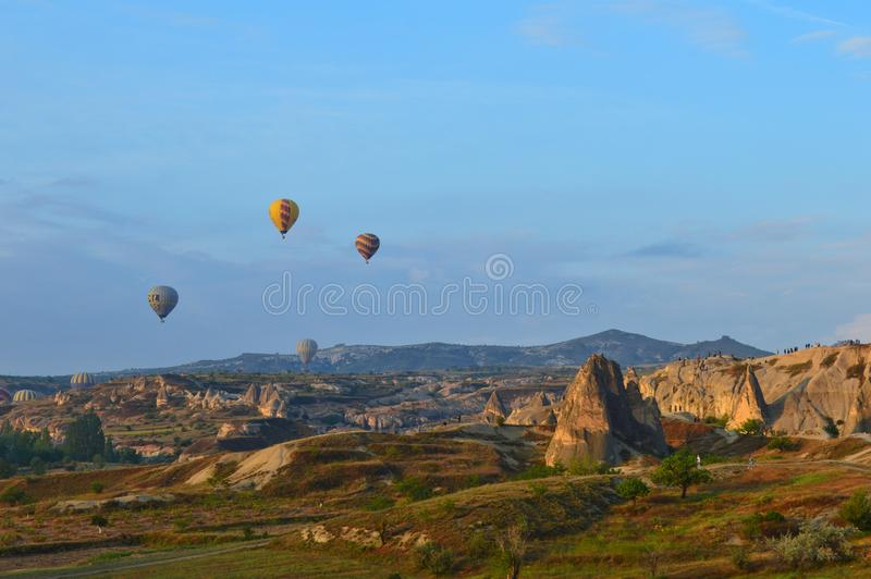 Hot air balloons in the background of a beautiful valley landscape in Cappadocia, Turkey royalty free stock photography