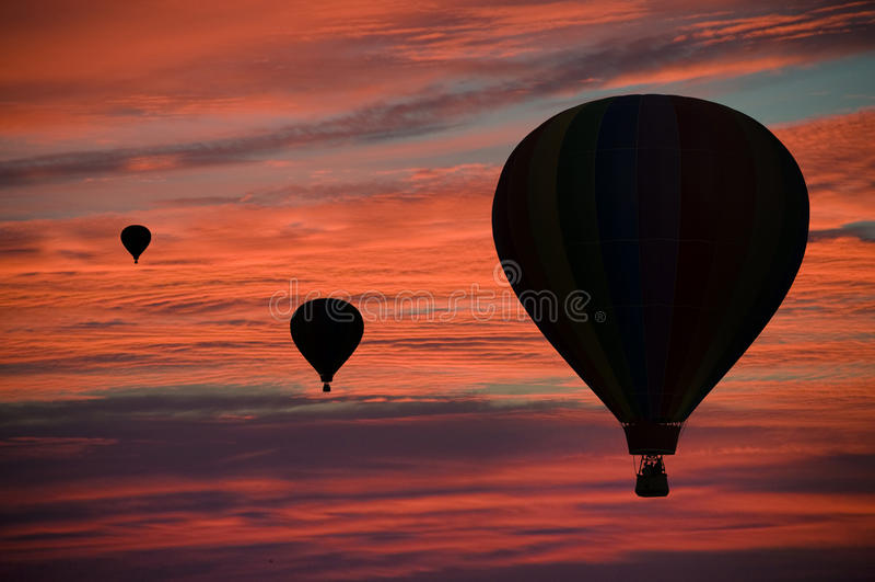 Hot-air balloons floating among clouds at dawn royalty free stock photo
