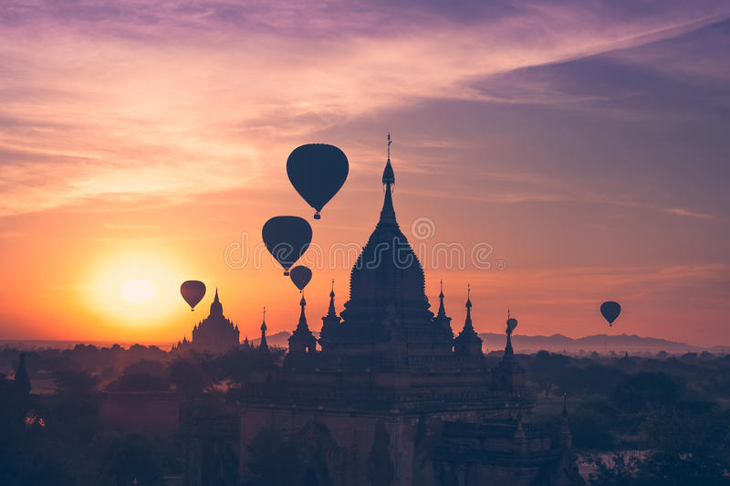 Hot air balloons flying over Buddhist Temples at Bagan. Myanmar. Amazing misty sunrise colors and balloons silhouettes over ancient Buddhist Temples at Bagan stock images