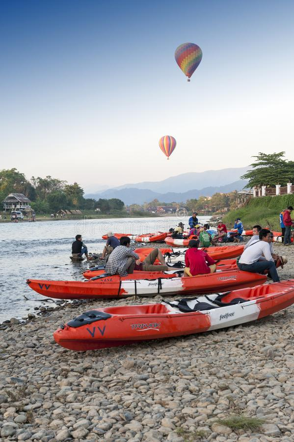 Hot air balloons flying over Nam Song River and tourist kayaks in Vang Vieng, popular resort town in Lao PDR. Vang Vieng, Laos - November 2015: Hot air balloons stock photos