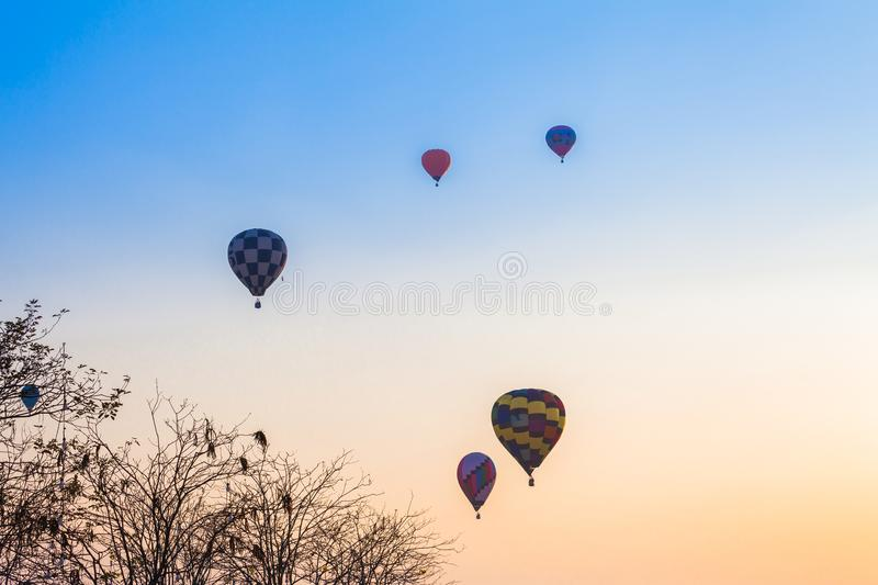 Hot air balloons flying in the sky at sunrise. Chiang Rai,Thailand - February 18,2018:hot air balloon flying above Singha park in Chiangrai Thailand. balloons royalty free stock images