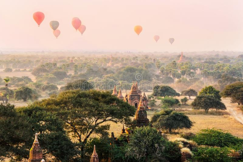 Hot air balloons in the morning sky on the background of the silhouette of  old Buddhist temple in Bagan, Myanmar royalty free stock photography
