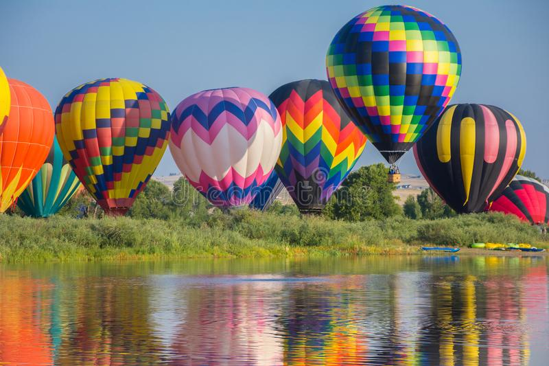 Hot Air Balloons By River. Colorful Reflections In Water stock images