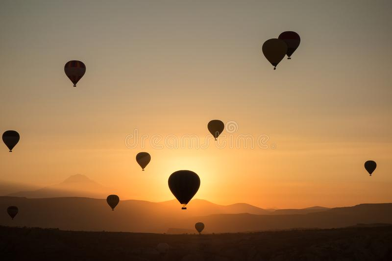 Hot air balloons in the sky during sunrise. Flying over the valley at Cappadocia, Anatolia, Turkey. Volcanic mountains in Goreme n royalty free stock image