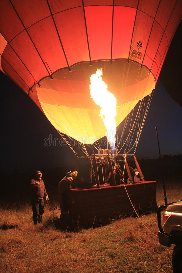 Woman climbs hot air balloon basket for adventure sport. Hot air and high temperature flame is thrown into the envelope of a hot air balloon to inflate it while