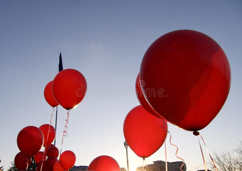 Hot air red ballons against blue sky with white fluffy clouds royalty free stock image