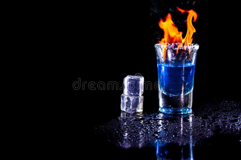 Hot alcoholic cocktail burning in shot glass with ice cubes.  stock image