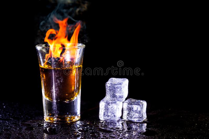 Hot alcoholic cocktail burning in shot glass with ice cubes.  stock photos