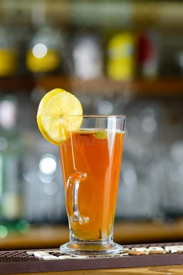 Hot alcoholic cocktail Grog with slice of lemon at glass at the. Bar counter, selective focus royalty free stock images