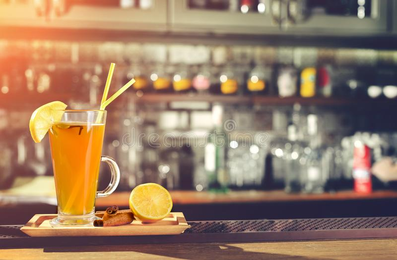 Hot alcoholic cocktail Grog with slice of lemon and straws at gl. Ass at the bar counter with copyspace for your text royalty free stock images