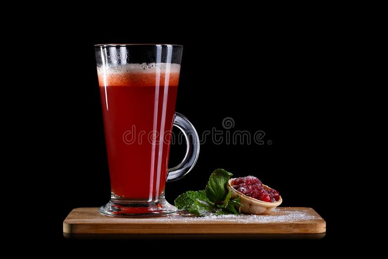 Hot alcoholic cocktail of sangria and cranberry nectar. Decorated with honey and lingonberry jam on black background stock image