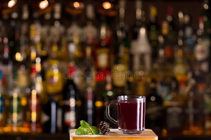 Hot alcoholic cocktail of sangria and cranberry nectar. Decorated with pinecone and mint on bar royalty free stock photos