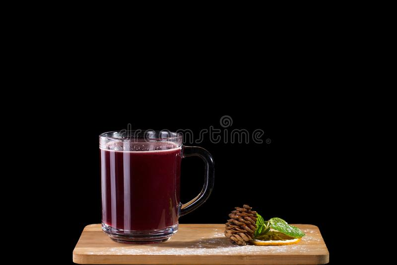 Hot alcoholic cocktail of sangria and cranberry nectar. Decorated with pinecone and mint isolated on black background stock photos