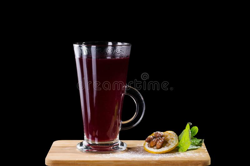 Hot alcoholic cocktail of sangria and cranberry nectar. Decorated with almonds, lemon and mint isolated on black background royalty free stock photo