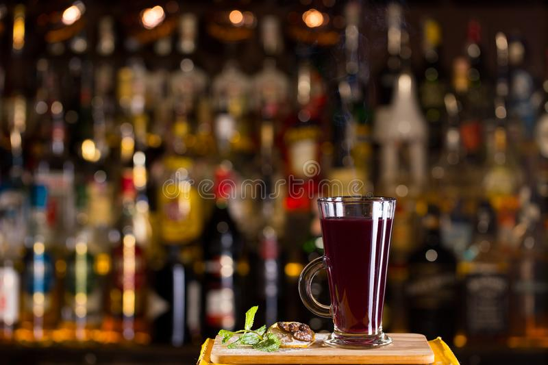 Hot alcoholic cocktail of sangria and cranberry nectar. Decorated with almonds, lemon and mint on bar stock photography