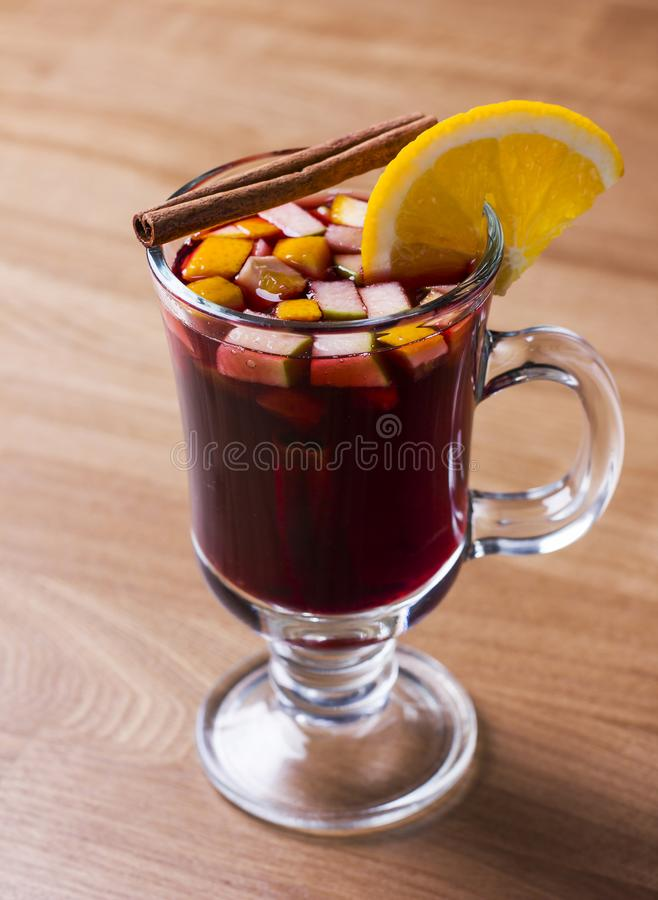 The hot alcoholic drink mulled wine on wooden background. The hot alcoholic drink on wooden background royalty free stock photos