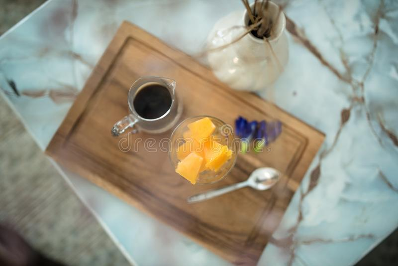 Hot americano coffee with iced mango cube.  royalty free stock image