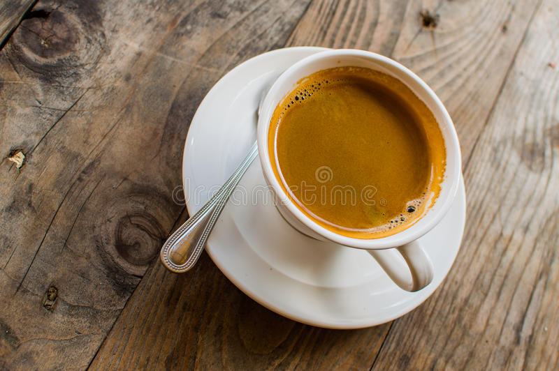 Hot Americano coffee in white cup on wooden table. This is how the makers of hot water mixed into the espresso. Americano is for t stock image