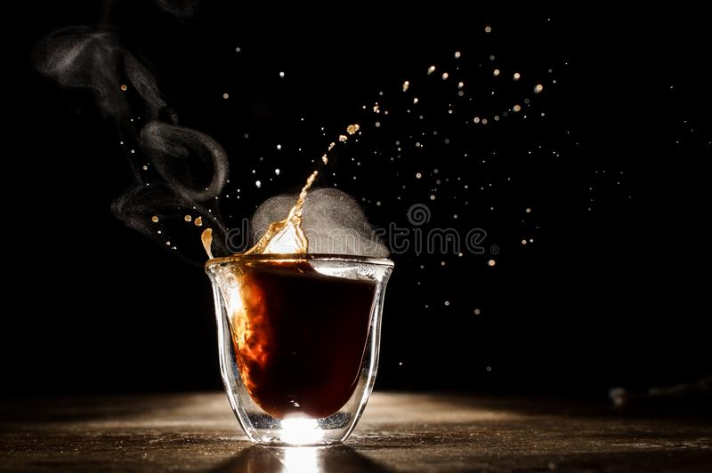 Hot and aromatic coffee spilling from glass cup stock photos