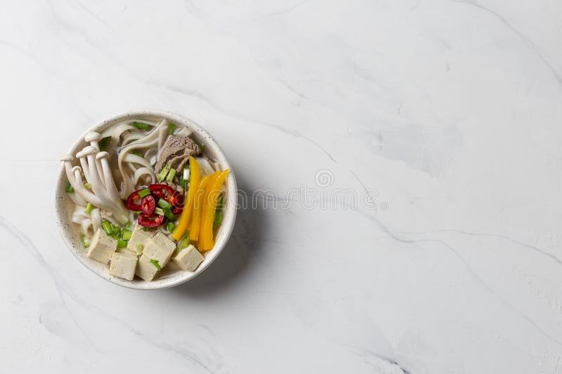 Hot asian noodle soup with beef, tofu mushrooms and vegetables. Heated noodle soup with beef, mushrooms and vegetables on white background. Copy space for text royalty free stock photography