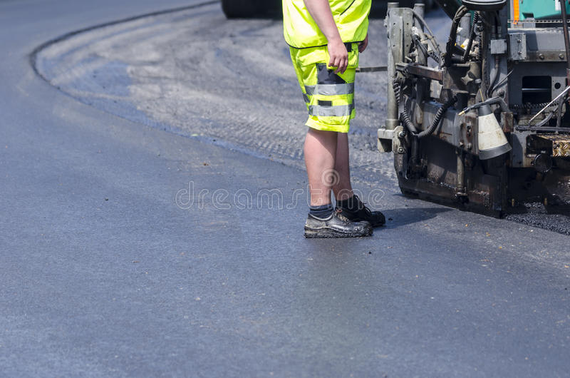 Hot asphalt work. Asphalt worker with high visibility clothing standing on hot new asphalt surface stock images