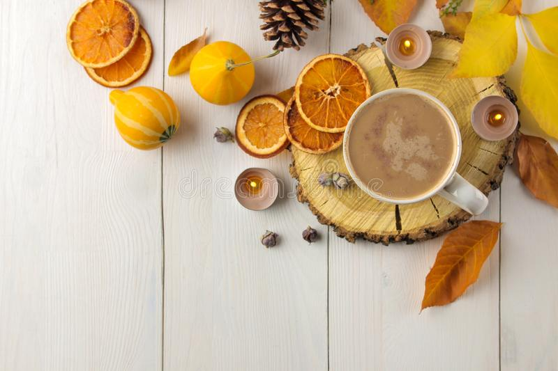 Hot autumn drink, coffee or cocoa, with yellow leaves and decorative pumpkins on a white wooden table. autumn composition. top vie. W royalty free stock photos