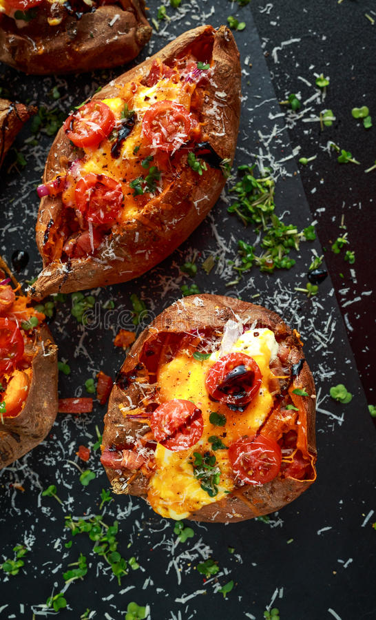 Hot baked sweet potato stuffed with bacon, cheddar cheese, cherry tomatoes, balsamic vinegar, cress salad and parmesan royalty free stock photography