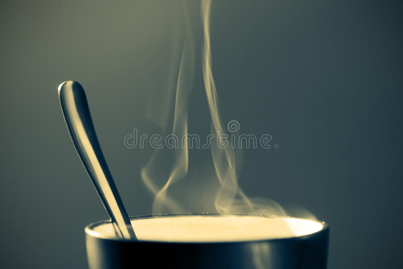 Hot beverage in a mug. Close up image of a mug containing hot beverage on a dark bluish background with vignette stock photography