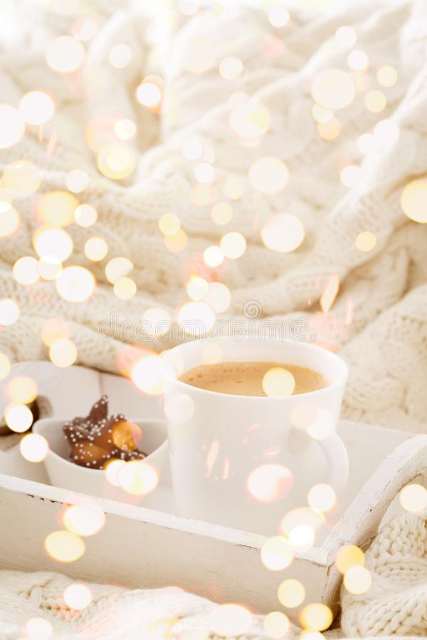 Hot beverage mug with chocolate cookies in a white wool blanket. Hot drink, cozy home and cold season concept. Vertical, bright lights bokeh background royalty free stock images