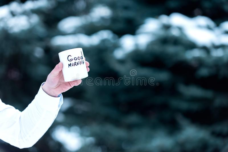 Hot beverage on nature background, defocused. Cup of tea or coffee with Good Morning inscription. Male hand holds white. Mug with drink. Morning drink outside stock images