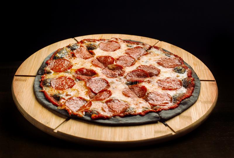 Hot big pepperoni pizza from black dough tasty. royalty free stock image