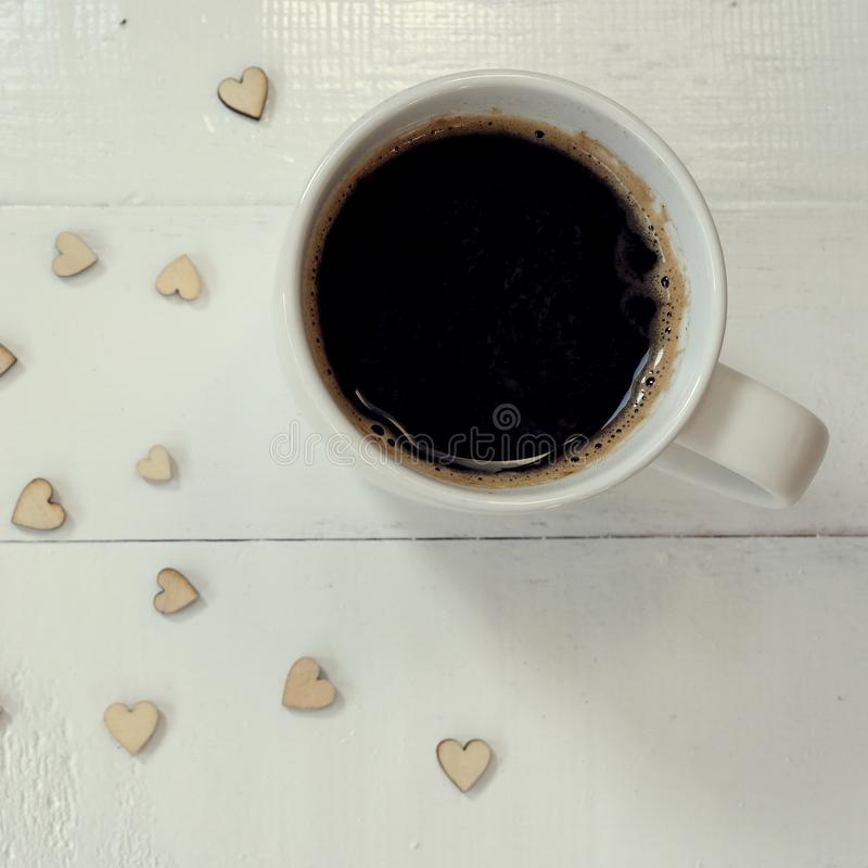 Hot black coffee with bubbles on top in white cup on white table decorated with mini heart, coffee love concept stock photo